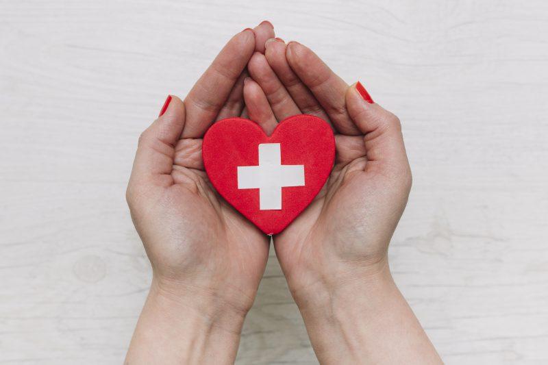 kobieta trzyma czerwone serce z papieru z białym krzyżem na środku