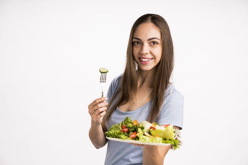 kobieta trzyma widelec i talerz z zdrowymi warzywami