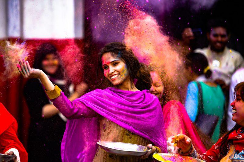 uśmiechnięta hinduska kobieta podrzuca przyprawy