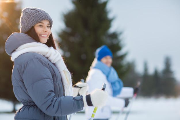 dwie kobiety ubrane w puchowe kurtki jeżdżą na nartach