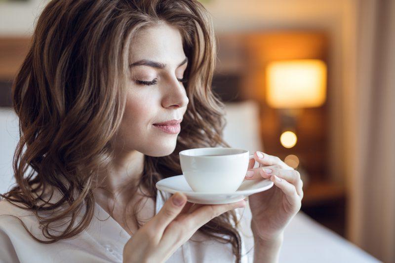 kobieta napawa się aromatem pysznej kawy