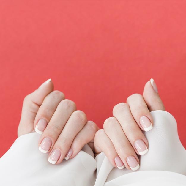 kobieta patrzy na swoje paznokcie