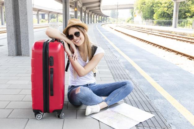kobieta siedzi z torbą na peronie