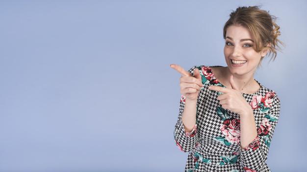 uśmiechnięta kobieta wskazuje punkt z przodu