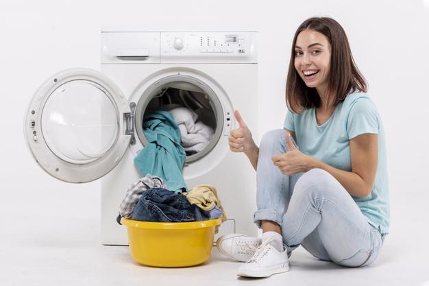 kobieta pierze ubrania w pralce