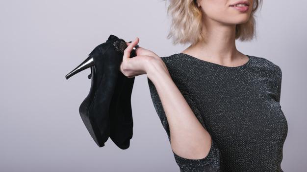 kobieta w szarej sukience trzyma czarne szpilki