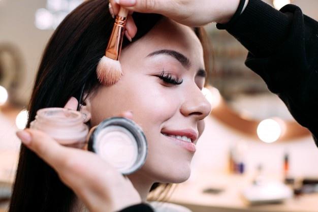 makijażysta wykonuje kobiecie makijaż twarzy