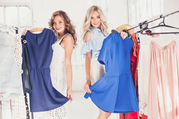 dwie kobiety trzymaja niebieskie sukienki