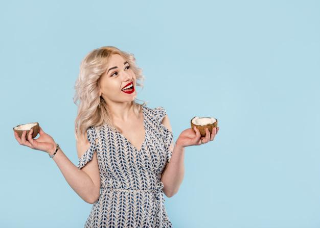 kobieta trzyma dwie polowki kokosa w dloniach