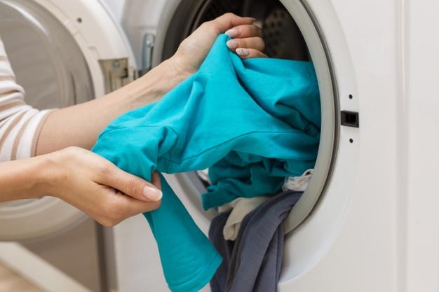 kobieta wyciaga pranie z pralki