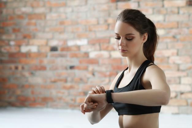 kobieta patrzy na sportowy zegarek