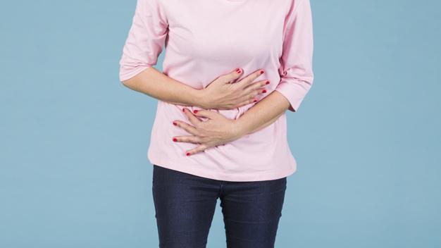kobieta w rozowym swetrze trzyma sie za brzuch