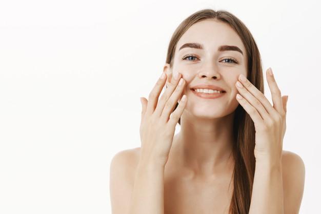 usmiechnieta kobieta dotyka twarzy