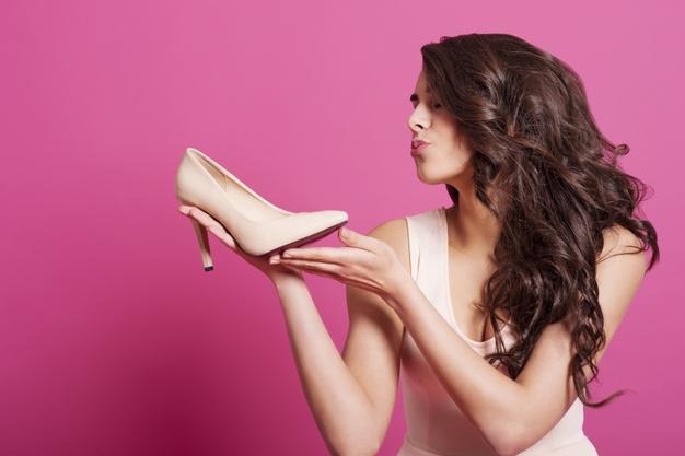 kobieta trzyma but szpilkę w dloniach