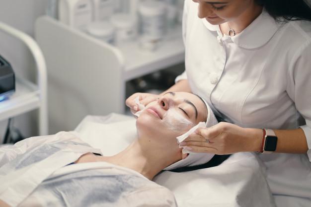 kosmetyczka oczyszcza twarz pacjentki